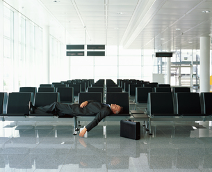 Businessman sleeping in airport loungeの写真素材 [FYI02130108]
