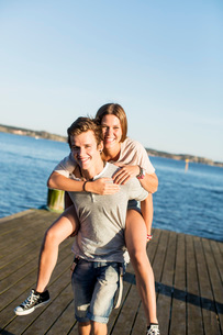 Young man giving woman a piggy back ride on pierの写真素材 [FYI02130139]
