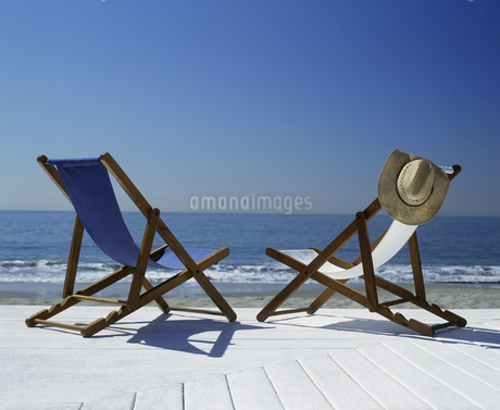 View of two lawn chairs on a deck overlooking the beachの写真素材 [FYI02130183]