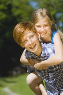 Boy and girl on piggyback, portraitの写真素材 [FYI02130208]
