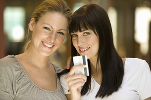 Two women holding credit cardの写真素材 [FYI02130258]