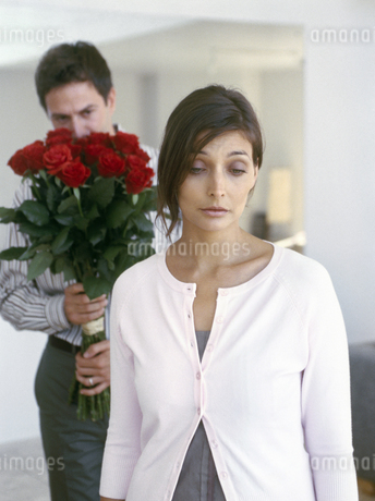 View of man holding roses with girlfriend in the foregroundの写真素材 [FYI02130312]