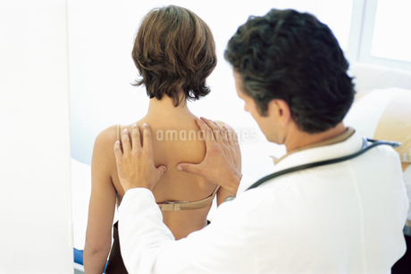 View of a male doctor checking a young woman's lungsの写真素材 [FYI02130344]