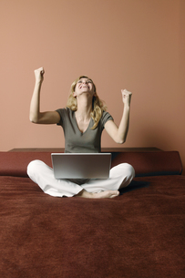 Portrait of a young woman celebrating her success on a laptopの写真素材 [FYI02130347]