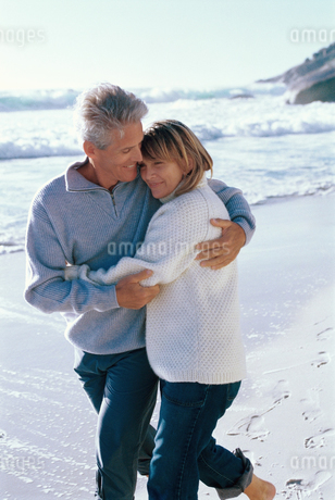 Mature couple embracing and walking on the beachの写真素材 [FYI02130393]