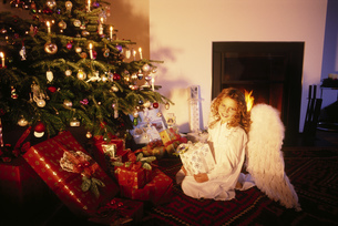 Young girl dressed as angel with Christmas treeの写真素材 [FYI02130397]