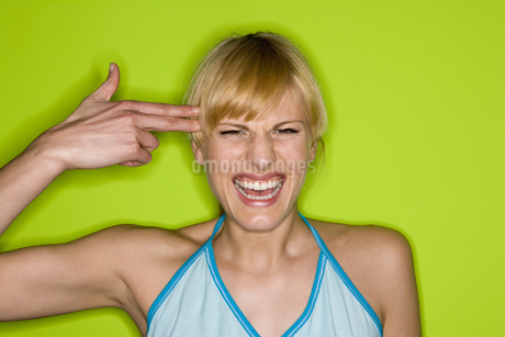 Woman mimicking gun with hand pointed at headの写真素材 [FYI02130432]