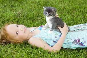Young girl with kitten in grassの写真素材 [FYI02130438]