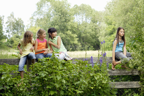 Young girls gossiping about friend outdoorsの写真素材 [FYI02130450]