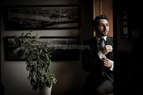 Mid adult businessman in suit adjusting sleeve while sittingの写真素材 [FYI02130467]