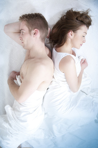 Young couple lying back to back in bedの写真素材 [FYI02130482]