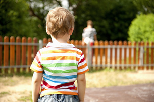 Young boy standing in playground, rear viewの写真素材 [FYI02130488]