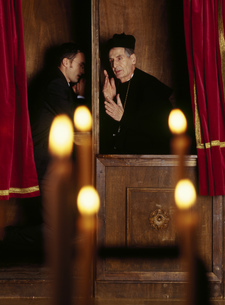 Businessman in confessional with priestの写真素材 [FYI02130555]