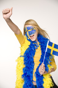 Young woman cheering with Swedish flag painted on faceの写真素材 [FYI02130570]