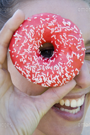 Close-up of woman looking through donut holeの写真素材 [FYI02130577]