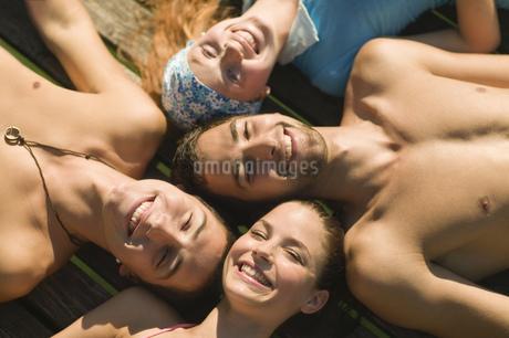 Teenagers sunbathing at lakeの写真素材 [FYI02130599]