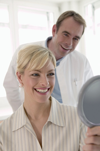 Woman smiling and looking mirror with dentistの写真素材 [FYI02130618]