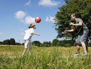 Father and son playing football outdoorsの写真素材 [FYI02130631]