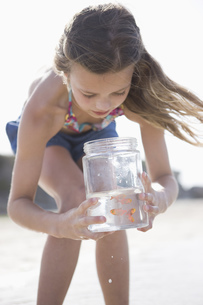 Girl looking at jar on beachの写真素材 [FYI02130662]