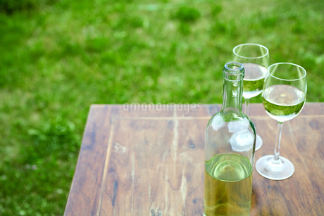 High angle view of wine bottle and glasses outdoorsの写真素材 [FYI02130663]