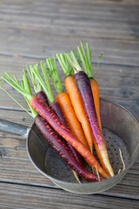 Fresh carrots in colander on wooden plankの写真素材 [FYI02130682]