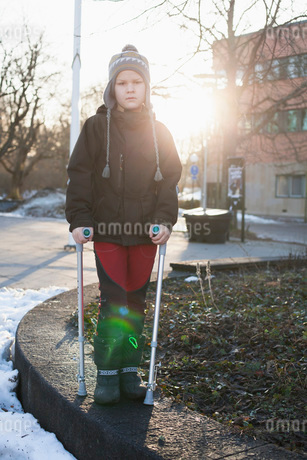 Portrait of disabled boy in warm clothing standing with crutの写真素材 [FYI02130707]