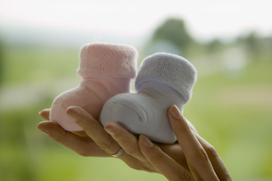 Woman holding up two baby bootsの写真素材 [FYI02130719]