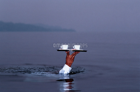 Submerged waiter carrying tray above waterの写真素材 [FYI02130759]