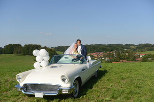 Portrait Of Bride And Groom In Open Top Car On Wedding Dayの写真素材 [FYI02130786]
