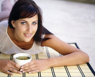 Woman lying on a straw mat holding a cup of teaの写真素材 [FYI02130788]