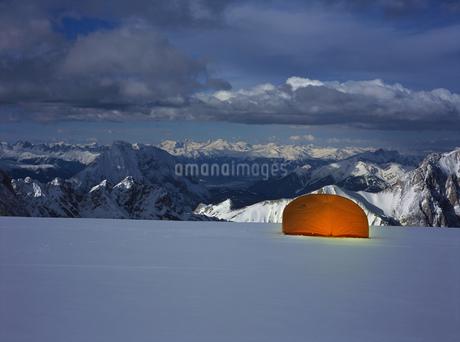 Illuminated tent on snowy mountain at duskの写真素材 [FYI02130830]