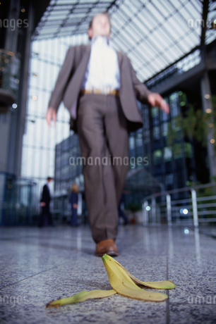 Businessman about to step on banana peelの写真素材 [FYI02130831]