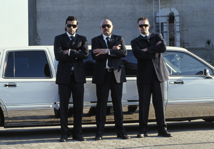Three men in suits with arms crossed in front of limousineの写真素材 [FYI02130855]