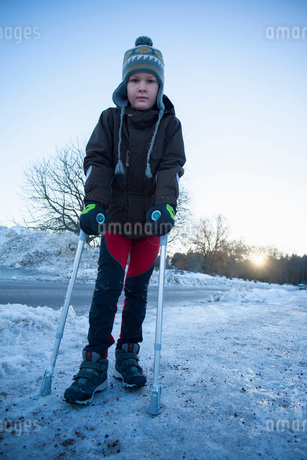 Portrait of disabled boy in warm clothing standing on snowyの写真素材 [FYI02130935]