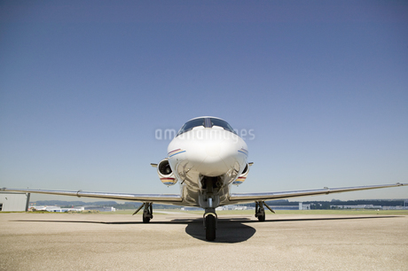 Front view of airplane on tarmac under blue skyの写真素材 [FYI02130962]