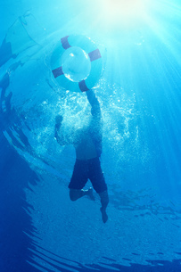 Underview, man swimming, holding onto life preserverの写真素材 [FYI02130988]