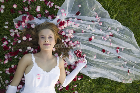 Bride laying in grass and flower petalsの写真素材 [FYI02131025]