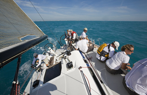 High angle view of group sitting on edge of sailboat in Key West, Florida, USAの写真素材 [FYI02131140]