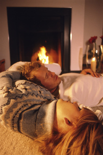 Young couple sleeping by fireplaceの写真素材 [FYI02131147]