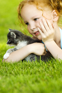 Young girl with kitten in grassの写真素材 [FYI02131157]