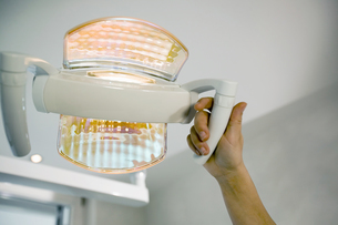 Dentist adjusting dental lightの写真素材 [FYI02131205]