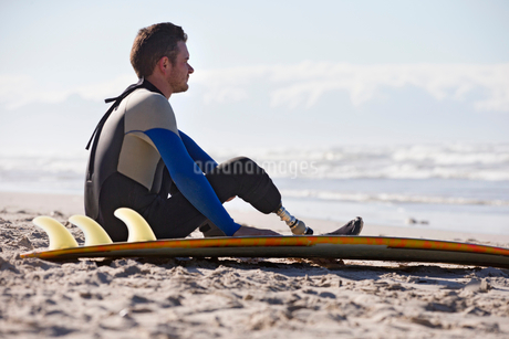 Surfer With Artificial Leg Sitting On Beachの写真素材 [FYI02131207]
