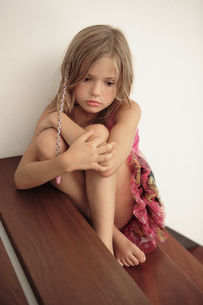 Sad girl hugging herself on stairsの写真素材 [FYI02131225]