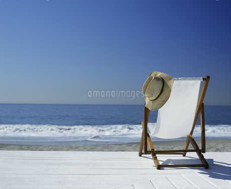 View of a lawn chair on a deck overlooking the beachの写真素材 [FYI02131236]