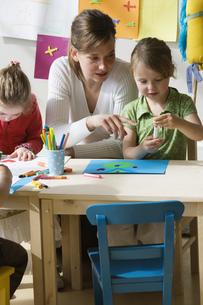 Preschool teacher helping girl with art projectの写真素材 [FYI02131263]
