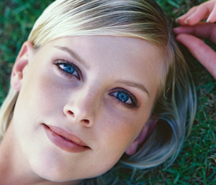 Close-up portrait of young woman lying in grassの写真素材 [FYI02131280]
