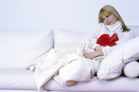 Sick woman relaxing with hot water bottleの写真素材 [FYI02131289]