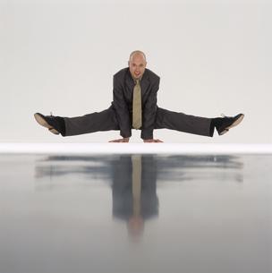 Businessman doing yoga, balancing on his handsの写真素材 [FYI02131294]