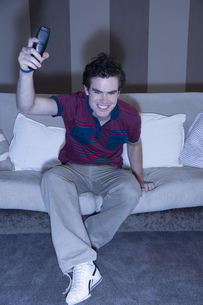 Young man watching television and cheeringの写真素材 [FYI02131341]