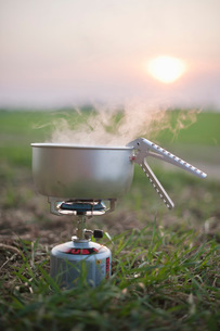 Food cooking in container on stove at fieldの写真素材 [FYI02131356]